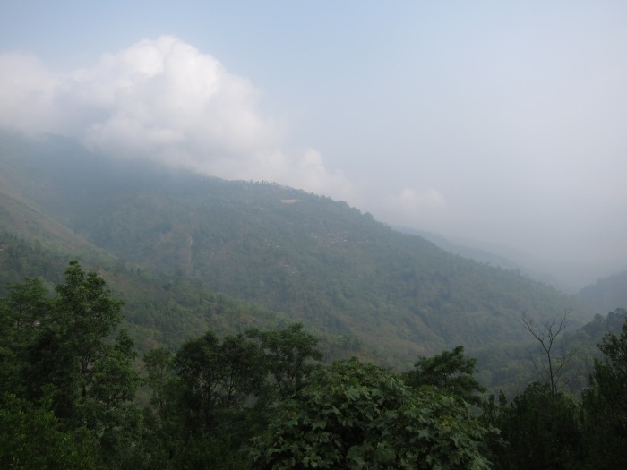 Behind the mist and the clouds, the immense Mount Kanchenjanga lurks in the distance.